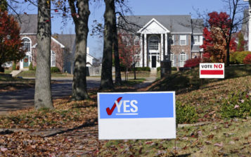 Voting signs in front of neighborhood homes