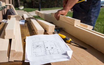 Carpenter working with technical blueprint drawing construction paper lying on outdoor