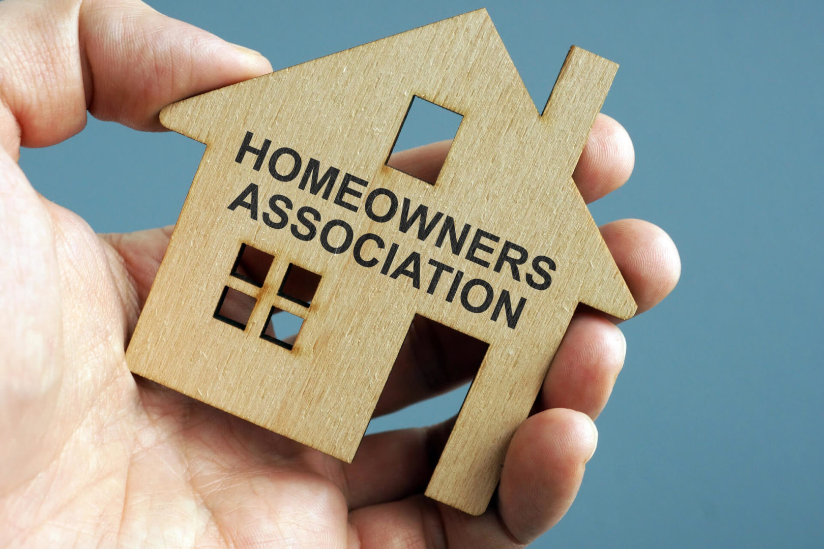 Man Holding House Shaped Wood With Homeowners Association Written On It